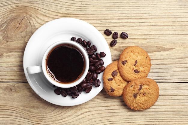 一杯のコーヒーとチョコレートクッキーのプレートの上面図