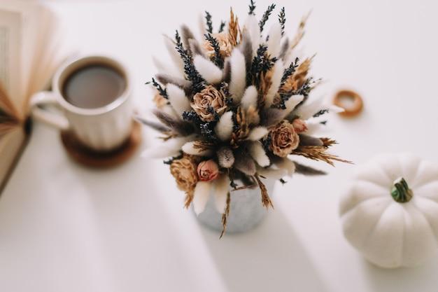 Вид сверху на чашку кофе и сушеные цветы на белом фоне.