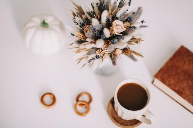 Вид сверху на чашку кофе и сушеные цветы на белом фоне. Premium Фотографии