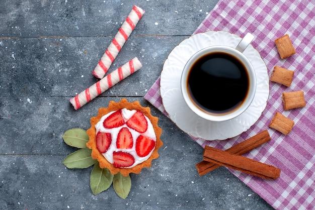 灰色の机の上のケーキとシナモン、コーヒーキャンディー甘い飲み物ココアクッキーと一緒に熱くて強いコーヒーのカップの上面図