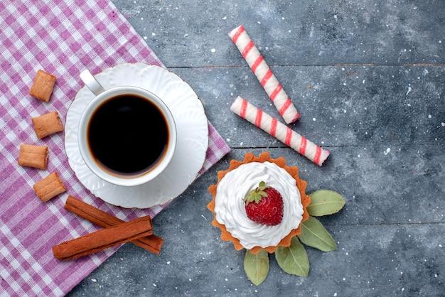 灰色の机の上のケーキとシナモン、コーヒー菓子の甘い飲み物と一緒に熱くて強いコーヒーのカップの上面図