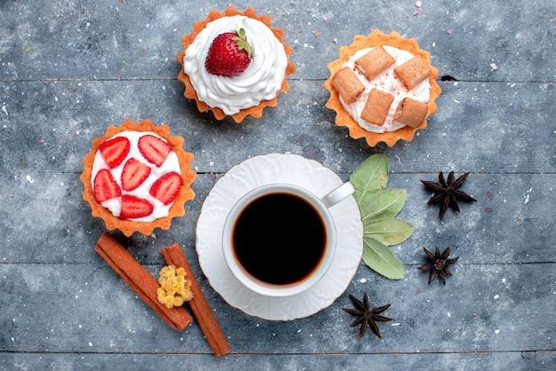 灰色のコーヒーキャンディーの甘い飲み物にケーキとシナモンと一緒に熱くて強いコーヒーのカップの上面図