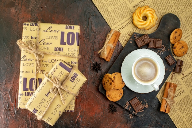 古い新聞のクッキーシナモンライムチョコレートバーの木製まな板の上のコーヒーの上面図暗い背景の美しいギフトボックス