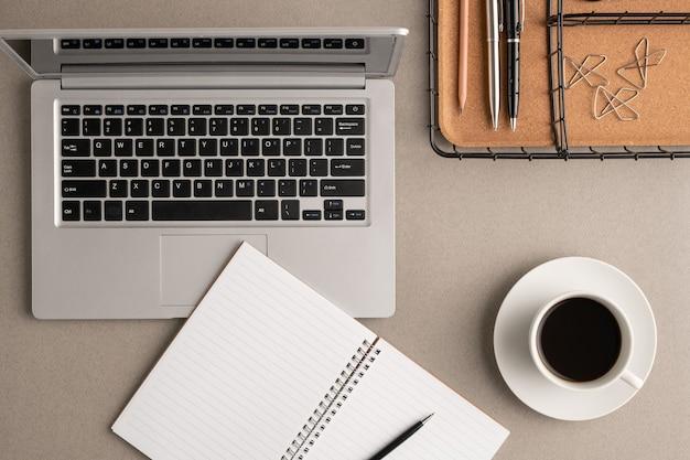 Вид сверху на чашку кофе, открытый блокнот с ручкой и пустыми страницами, ноутбук и корзину с зажимами и другими канцелярскими принадлежностями на рабочем месте