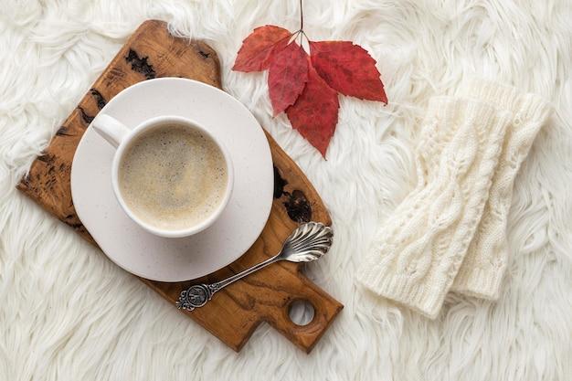 Вид сверху на чашку кофе с осенним листом и ложкой