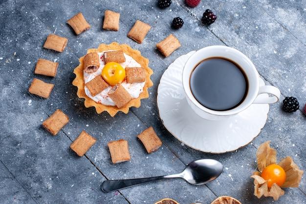 Вид сверху на чашку кофе со сливочной подушкой для торта в форме печенья вместе с ягодами на сером, ягодном бисквитном печеньке, цвет фото