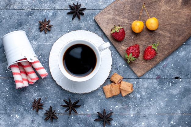 明るい机の上の新鮮な赤いイチゴクッキーピンクスティックキャンディー、クッキーキャンディーコーヒービスケットベリーとコーヒーの上面図