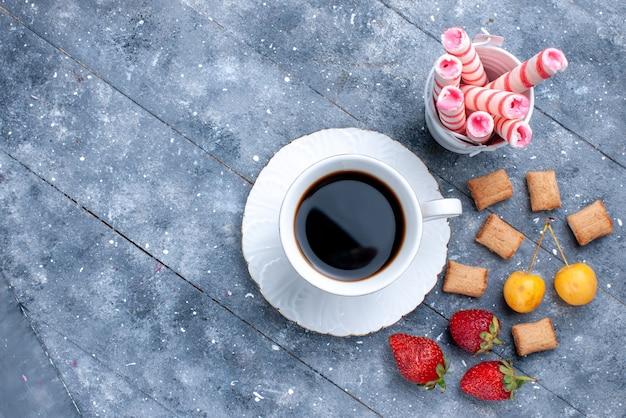明るい机の上のイチゴクッキーピンクスティックキャンディー、クッキーキャンディーコーヒー写真とコーヒーの上面図