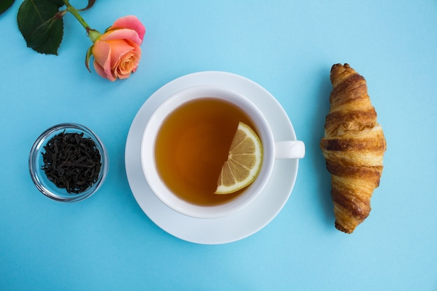 Вид сверху на чашку горячего черного чая, круассан и розовую розу
