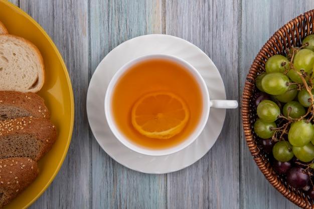 Вид сверху чашки горячего тодди с ломтиками хлеба в тарелке и корзиной винограда на деревянном фоне