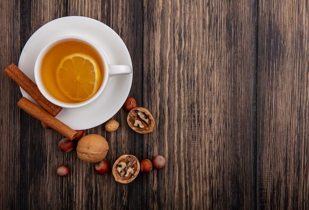 Вид сверху чашки горячего тодди с корицей на блюдце и орехами грецкими орехами на деревянном фоне с копией пространства