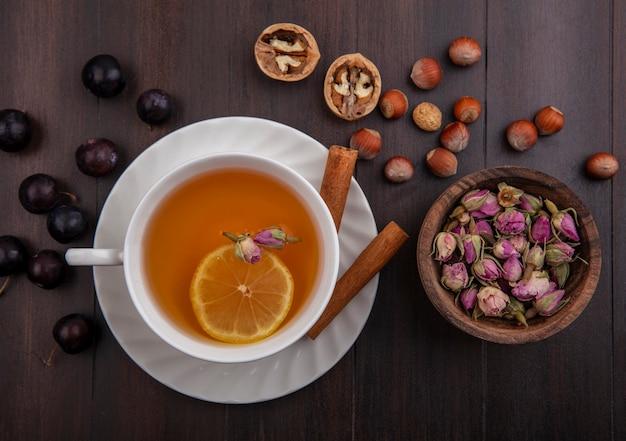 Вид сверху на чашку горячего тодди с цветком лимона внутри и корицей на блюдце с рисунком ягод терна, орехов и грецких орехов и вазу с цветами на деревянном фоне