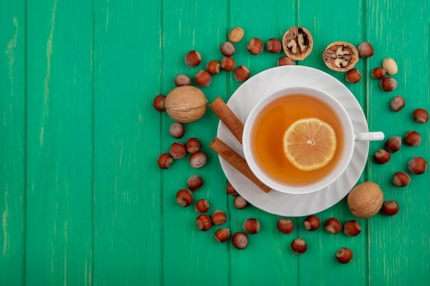 Вид сверху на чашку горячего тодди с лимоном внутри и корицей на блюдце с рисунком из орехов и грецких орехов на зеленом фоне с копией пространства