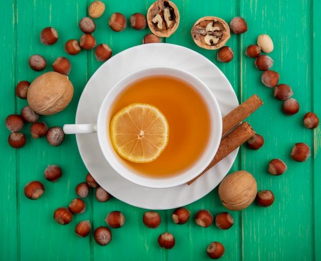 Вид сверху на чашку горячего тодди с лимоном внутри и корицей на блюдце с узором из орехов и грецких орехов на зеленом фоне