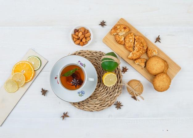 Вид сверху на чашку чая и цитрусовые на круглой подставке для посуды с печеньем на разделочной доске, цитрусовые и миску с миндалем на белой поверхности