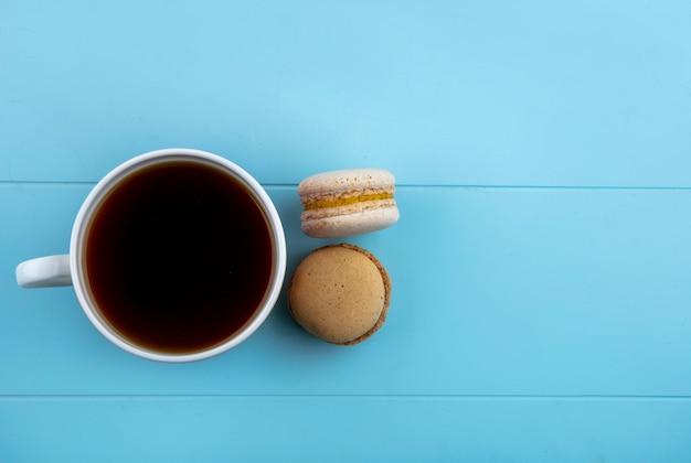 コピースペースと青色の背景にお茶とクッキーのサンドイッチのトップビュー