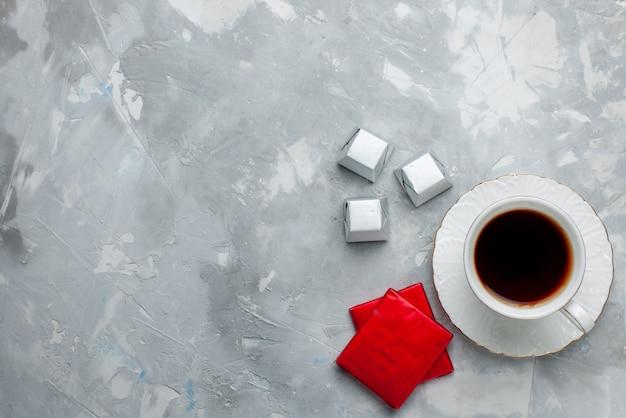 Вид сверху на чашку горячего чая внутри белой чашки на стеклянной тарелке с серебряным пакетом шоколадных конфет на светлом столе, чайный напиток, сладкое шоколадное печенье