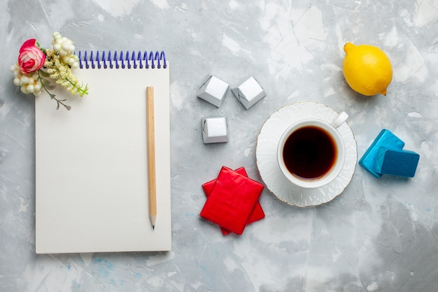 Вид сверху на чашку горячего чая внутри белой чашки с серебряным пакетом шоколадных конфет, блокнот на светлом столе, пить сладкий чай