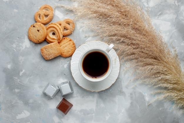 Вид сверху на чашку горячего чая с шоколадом и печеньем на свете, печенье, конфеты, шоколадное чайное печенье