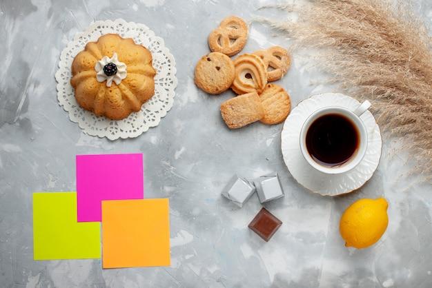 Вид сверху на чашку горячего чая с шоколадным лимонным пирожным и печеньем на свету, сладкое печенье, конфеты