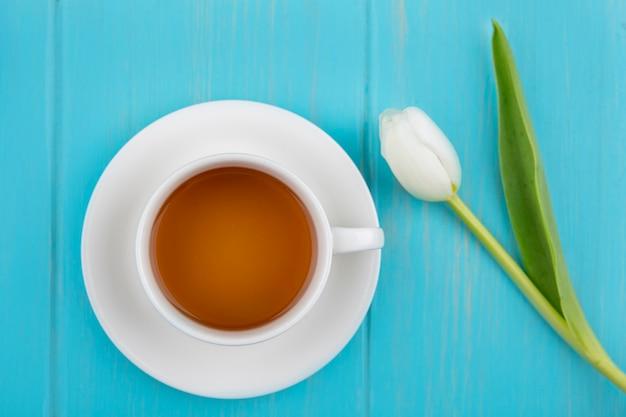Вид сверху чашки чая на блюдце и цветок на синем фоне