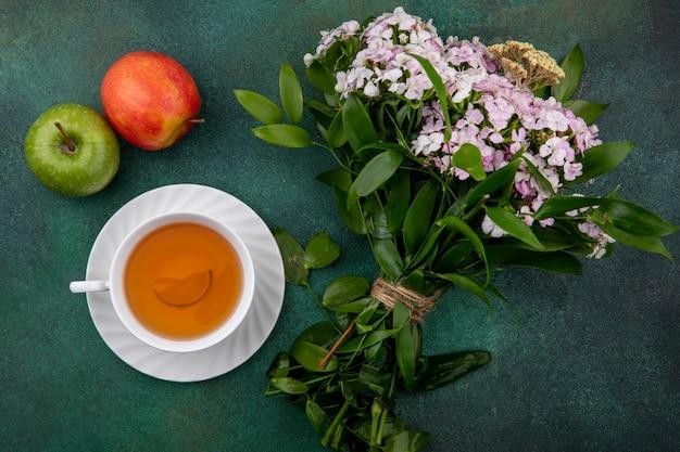 Вид сверху на чашку чая с яблоками и букет цветов на зеленой поверхности