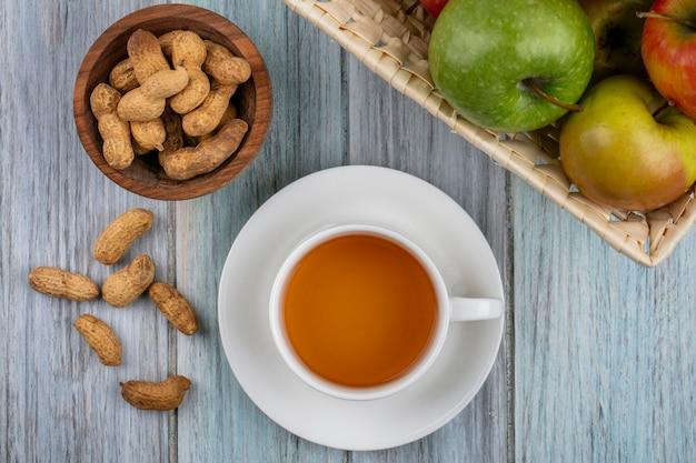 灰色の表面にバスケットにリンゴとボウルにピーナッツとお茶のカップのトップビュー