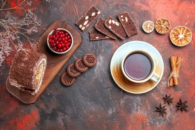 暗い表面にビスケットロールとお茶の上面図