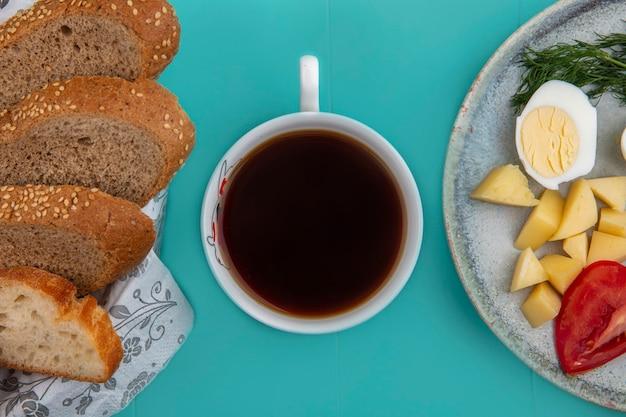 青い背景の上のパンとエッグポテトトマトディルとお茶の上面図