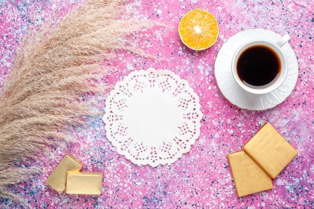 ピンクの表面にチョコレート菓子とお茶の上面図