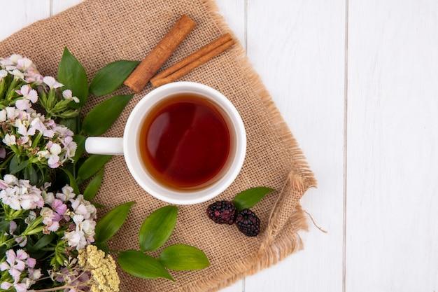 Вид сверху на чашку чая с корицей и цветами на бежевой салфетке на белой поверхности