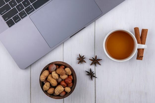 Вид сверху на чашку чая с корицей и орехами в миске и с ноутбуком на белой поверхности