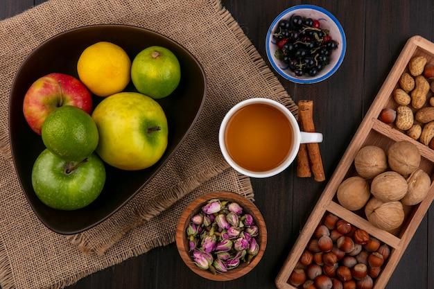 Вид сверху чашки чая с корицей, яблоками и орехами на деревянной поверхности