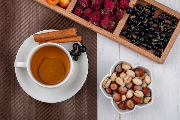 Вид сверху на чашку чая с корицей, черной смородиной, малиной, белой вишней и орехами на белой поверхности