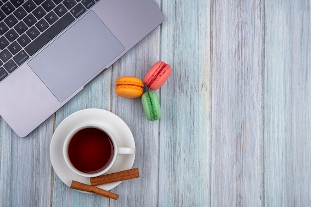 Вид сверху на чашку чая с macarons цвета корицы и ноутбуком на серой поверхности