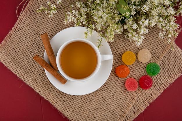 Вид сверху на чашку чая с мармеладом цвета корицы и цветами на бежевой салфетке