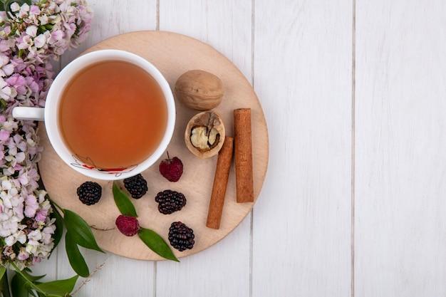 Вид сверху на чашку чая с корицей, орехами, малиной и ежевикой на подставке с цветами на белой поверхности