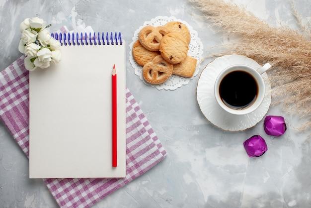 グレーホワイトのクッキービスケットスウィートティーシュガーにおいしい小さなクッキーチョコレートキャンディーとお茶の上面図
