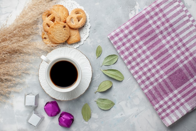 Вид сверху на чашку чая с вкусным маленьким печеньем, шоколадные конфеты на свете, печенье, печенье, сладкий чай, сахар