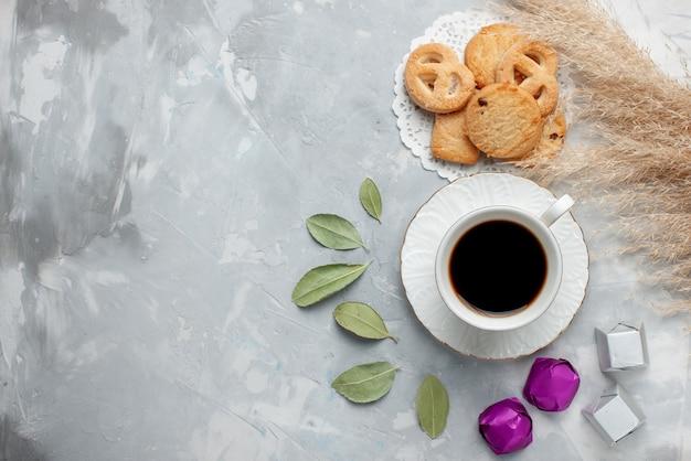 Вид сверху на чашку чая с вкусным маленьким печеньем, шоколадные конфеты на светлом полу, печенье, печенье, сладкий чай, сахар