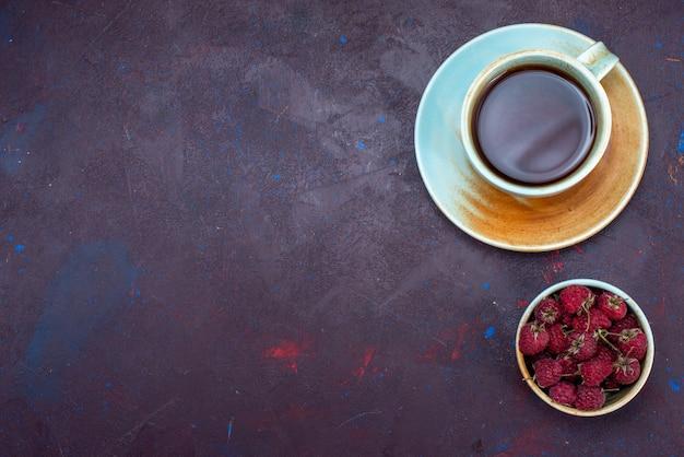 Вид сверху на чашку чая со свежей малиной на темной поверхности