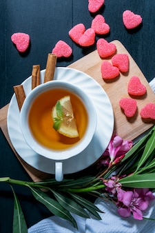 Вид сверху чашки чая с ломтиком лимона и корицы на блюдце и мармелад на разделочной доске с цветами и листьями с тканью на синем фоне