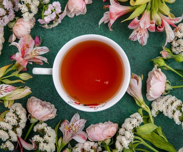 緑の表面に光のピンクの花とお茶のカップのトップビュー
