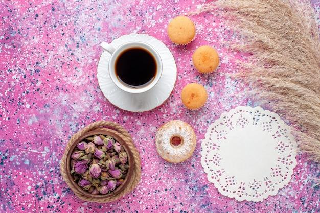 ピンクの表面に小さなケーキとお茶の上面図
