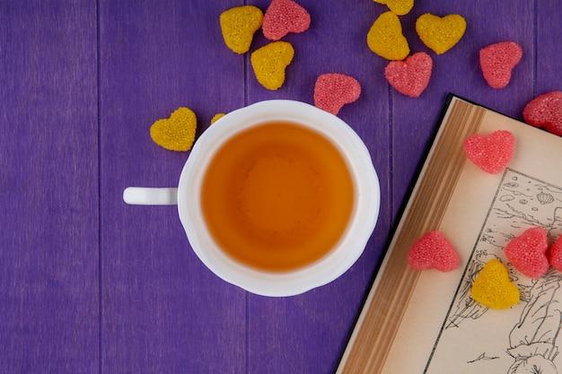 Вид сверху чашки чая с мармеладом и открытой книгой на фиолетовом фоне