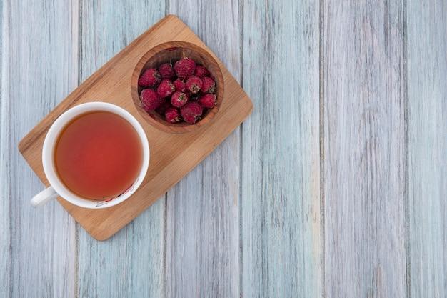 Вид сверху на чашку чая с малиной на разделочной доске на серой поверхности