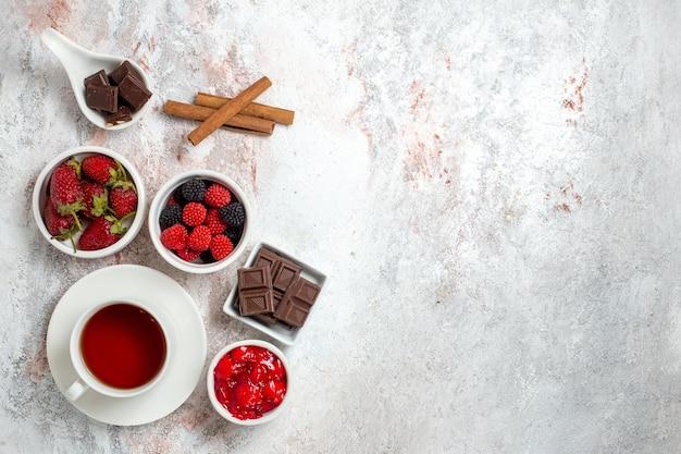 Вид сверху на чашку чая с клубничным вареньем и конфитюрами на белой поверхности