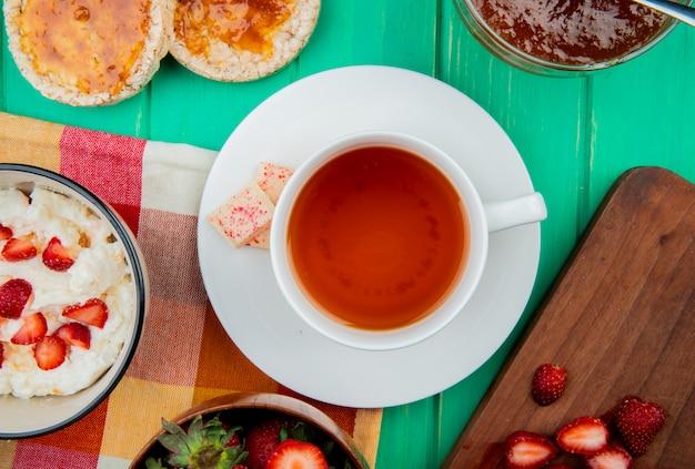 Вид сверху чашка чая с белым шоколадом на пакетик и миску творога с хрустящими хлебцами и персиковым джемом на зеленой поверхности