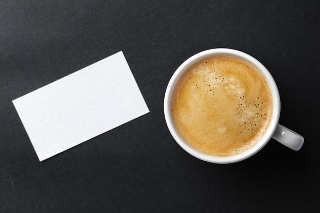 エスプレッソと白のビジネスカードとカップのトップビュー