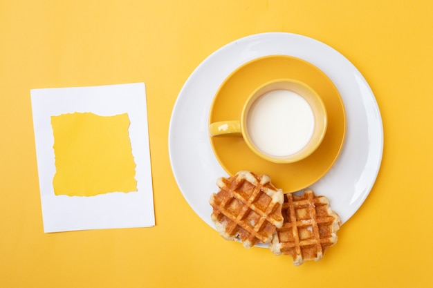 牛乳とカップと黄色の背景に、左側にコピースペースを持つ黄色の四角い紙とワッフルのトップビュー